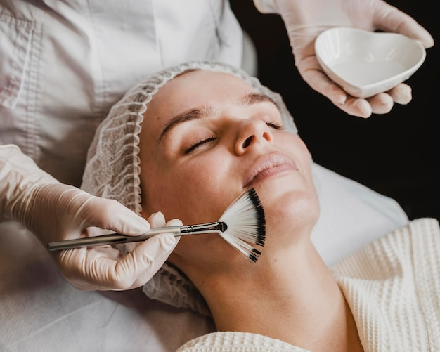 Young beautiful woman getting a face skin treatment at the spa