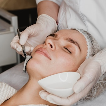 Giovane bella donna che ottiene un trattamento della pelle del viso