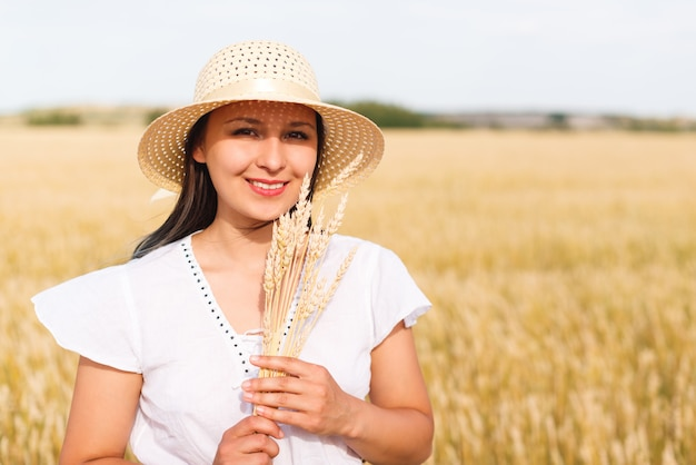 Young beautiful woman in golden wheat field. concept of summer, freedom, warmth, harvest, agriculture