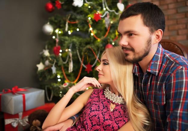 젊은 아름다운 여인이 크리스마스에 남편의 예기치 않은 선물로 그녀의 머리를 잡았습니다.