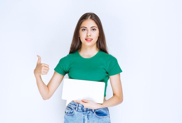 Giovane bella donna in camicia verde che mostra la cornice vuota del discorso su sfondo bianco.
