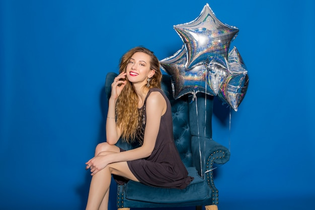 Young beautiful woman in grey dress sitting on a blue armchair with silver balloons