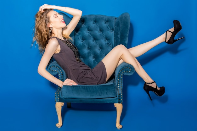 Young beautiful woman in grey dress sitting on a blue armchair