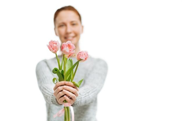 젊은 아름 다운 여자 회색 스웨터 흰색 바탕에 핑크 튤립을 제공합니다. 흐림 초상화, 선택적 초점.