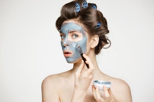 Giovane bella donna in bigodini che copre il viso di mack. trattamento facciale. cosmetologia e spa di bellezza.