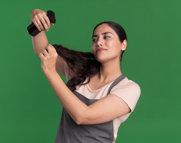 Young beautiful woman hairdresser in apron holding applying moisturising spray to her hair looking confident standing over green wall