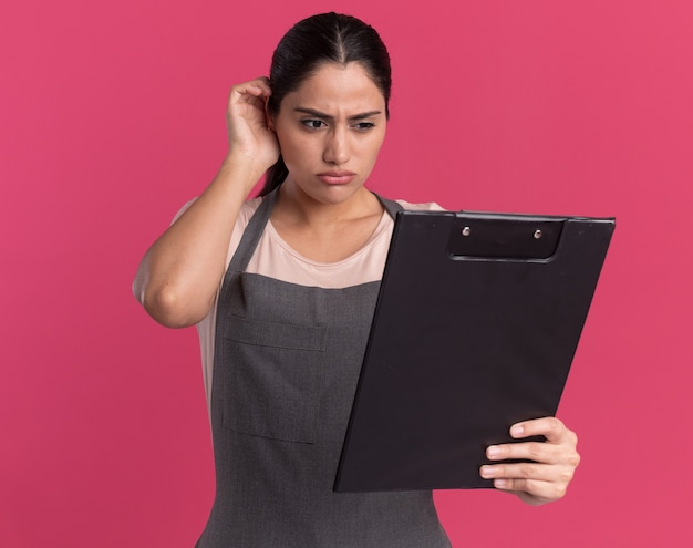 Parrucchiere di giovane bella donna in grembiule che tiene appunti guardandolo con faccia seria in piedi sopra il muro rosa