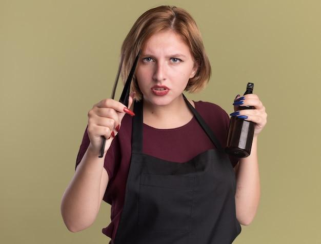Parrucchiere di giovane bella donna in grembiule che tiene la bottiglia spray per capelli e pettine guardando davanti con faccia seria in piedi sopra la parete verde