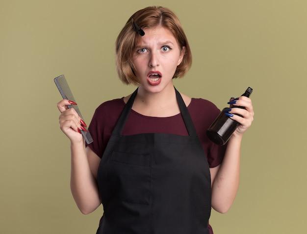Parrucchiere di giovane bella donna in grembiule che tiene pettine per capelli e flacone spray guardando davanti confuso e dispiaciuto in piedi sopra la parete verde