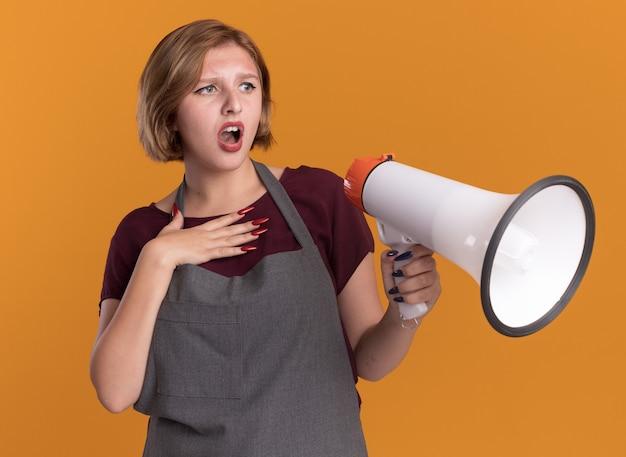 Parrucchiere di giovane bella donna in grembiule che tiene il megafono che osserva da parte confuso e sorpreso in piedi sopra la parete arancione