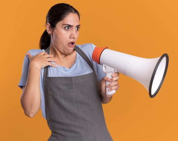 Parrucchiere di giovane bella donna in grembiule che tiene il megafono che osserva da parte confuso e preoccupato in piedi sopra la parete arancione