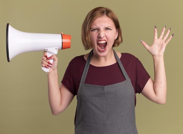 Parrucchiere della giovane bella donna in grembiule che tiene il megafono che grida con l'espressione aggressiva che diventa selvaggio in piedi sopra la parete verde