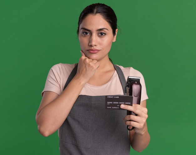 Giovane bella donna parrucchiere in grembiule che tiene trimmer e carta di credito guardando davanti con la mano sul mento con espressione fiduciosa in piedi sopra la parete verde
