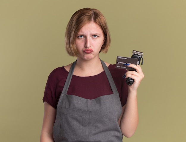Young beautiful woman hairdresser in apron holding trimmer and credit card looking at front with sad expression standing over green wall