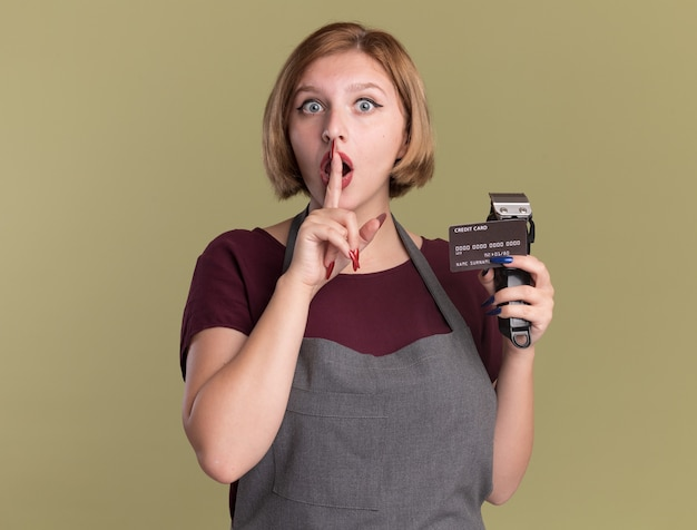 Parrucchiere di giovane bella donna in grembiule che tiene trimmer e carta di credito facendo gesto di silenzio con il dito sulle labbra guardando sorpreso in piedi sopra la parete verde