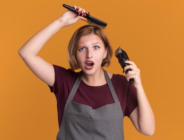 Parrucchiere di giovane bella donna in grembiule che tiene trimmer e spazzola per capelli che pettina i capelli che sembrano confusi e sorpresi in piedi sopra la parete arancione