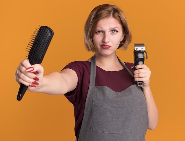Parrucchiere di giovane bella donna in grembiule che tiene trimmer e spazzola per capelli guardando la parte anteriore rendendo la bocca ironica essendo dispiaciuto in piedi sopra la parete arancione