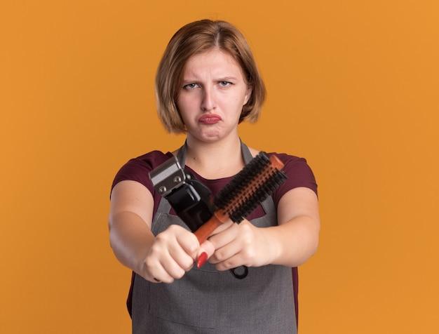 Parrucchiere di giovane bella donna in grembiule che tiene trimmer e spazzola per capelli guardando davanti rendendo la bocca ironica displesed attraversando le mani in piedi sopra la parete arancione