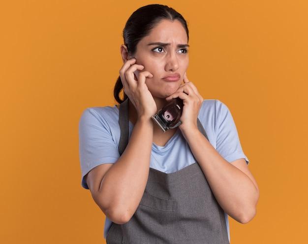 Parrucchiere di giovane bella donna in grembiule che tiene il trimmer che osserva da parte confuso e scontento sulla parete arancione