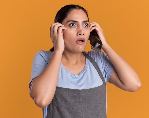 Giovane bella donna parrucchiere in grembiule tenendo il trimmer guardando da parte spaventato e preoccupato per la parete arancione
