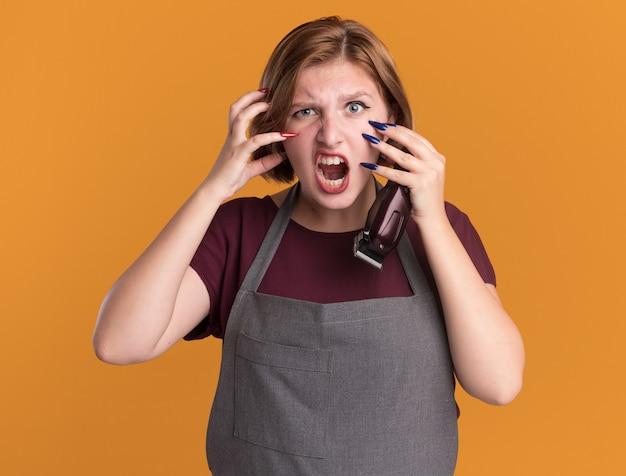 Parrucchiere di giovane bella donna in grembiule che tiene trimmer guardando davanti gridando con faccia arrabbiata pazzo pazzo e frustrato in piedi sopra la parete arancione
