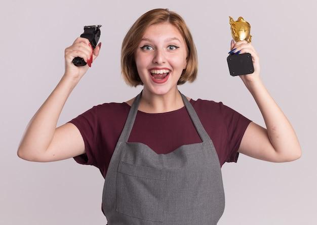 Parrucchiere di giovane bella donna in grembiule che tiene macchina trimmer e trofeo d'oro guardando davanti felice ed eccitato in piedi sopra il muro bianco