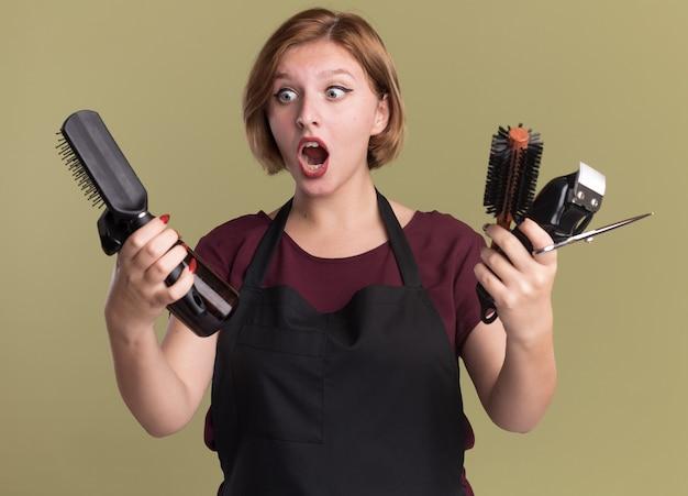 Giovane bella donna parrucchiere in grembiule che tiene trimmer con spazzola per capelli e flacone spray guardando confuso e sorpreso in piedi sopra la parete verde