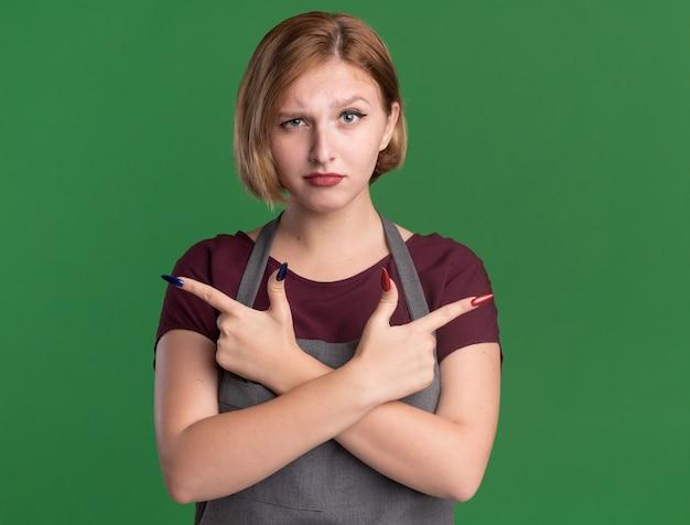 Parrucchiere di giovane bella donna in grembiule guardando davanti con faccia seria incrociando le mani che puntano con il dito indice ai lati in piedi sopra la parete verde