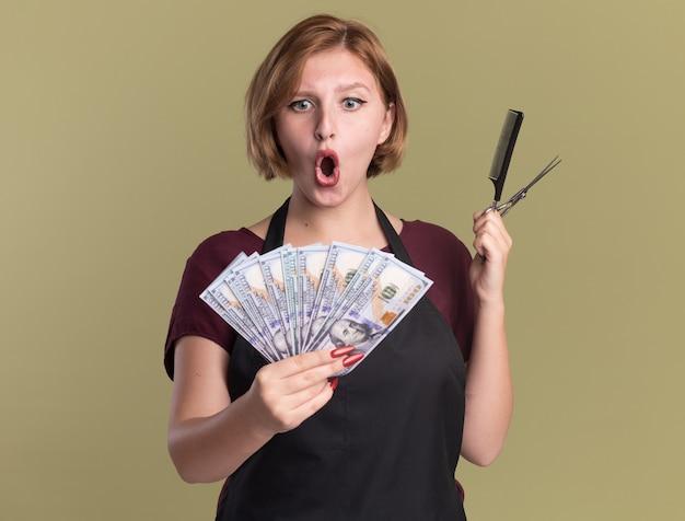 Parrucchiere della giovane bella donna in grembiule che mostra il pettine e le forbici dei capelli della tenuta dei contanti che sembrano sorpresi e felici che stanno sopra la parete verde