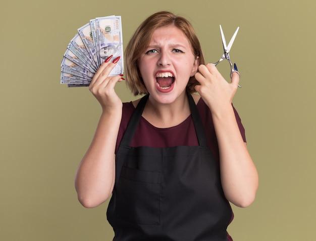 Parrucchiere della giovane bella donna in grembiule che mostra le forbici della tenuta dei contanti che gridano eccitato e confuso che si leva in piedi sopra la parete verde