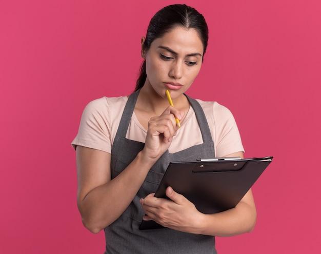 Parrucchiere di giovane bella donna in grembiule con la matita che tiene appunti guardandolo con la faccia seria che sta sopra la parete rosa