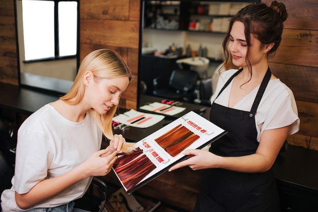 Young beautiful woman and hairdresser comparing her blonde hair with color hair