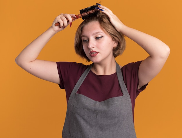 Молодая красивая женщина-парикмахер в фартуке расчесывает волосы щеткой, глядя в сторону с серьезным лицом, стоящим над оранжевой стеной
