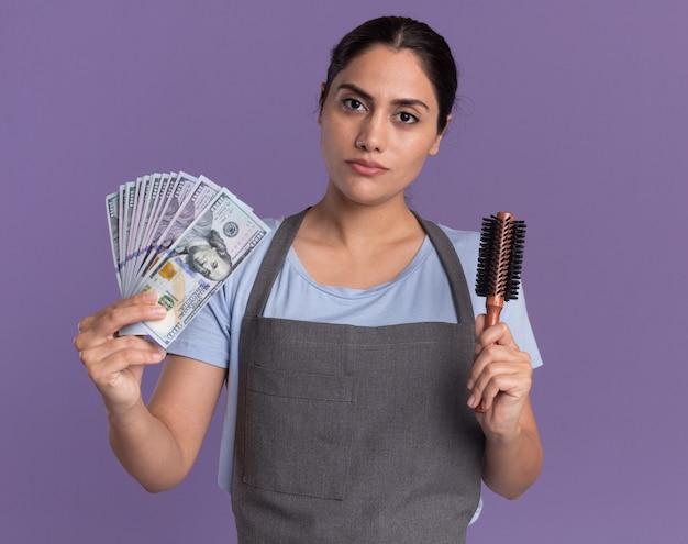보라색 벽 위에 서 심각한 얼굴로 앞에 찾고 현금 및 헤어 브러시를 들고 앞치마에 젊은 아름 다운 여자 미용사