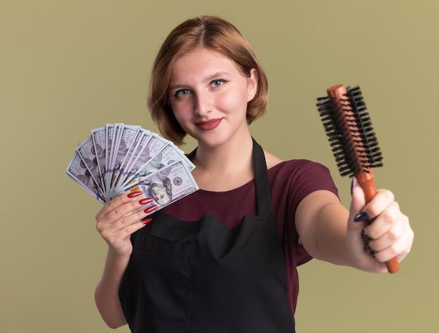 Молодая красивая женщина-парикмахер в фартуке держит деньги, показывая щетку для волос, уверенно улыбаясь, стоя над зеленой стеной