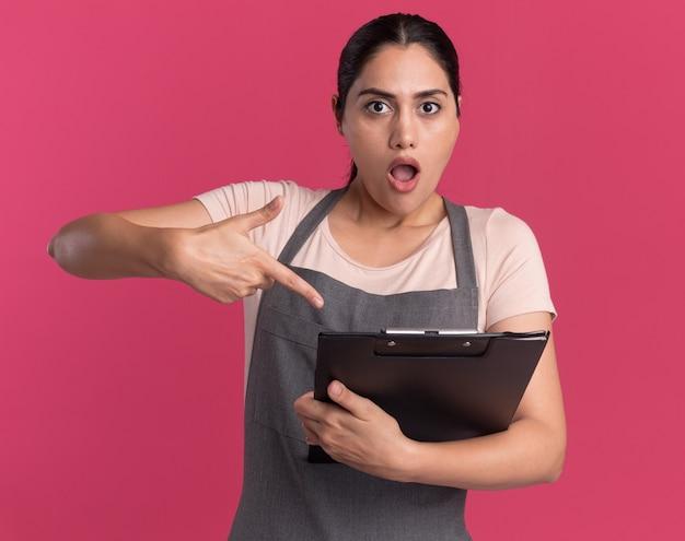 검지 손가락으로 가리키는 클립 보드를 들고 앞치마에 젊은 아름 다운 여자 미용사 혼란스럽고 핑크 벽 위에 서 놀란