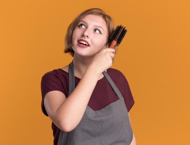 머리를 빗질 머리를 들고 앞치마에 젊은 아름 다운 여자 미용사 오렌지 벽 위에 서 웃 고 옆으로 찾고