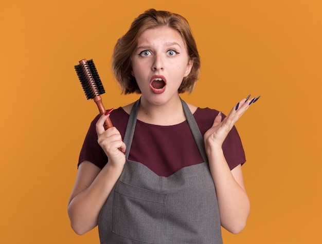 앞치마 머리 브러시를 들고 앞치마에 젊은 아름 다운 여자 미용사 오렌지 벽 위에 서 깜짝 놀라게하고 놀란