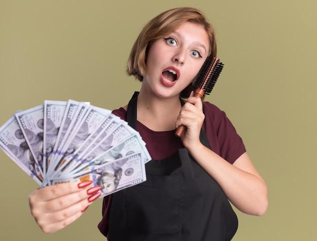 앞치마에 젊은 아름 다운 여자 미용사 머리 브러시를 들고 현금을 보여주는 혼란과 녹색 벽 위에 서 놀란