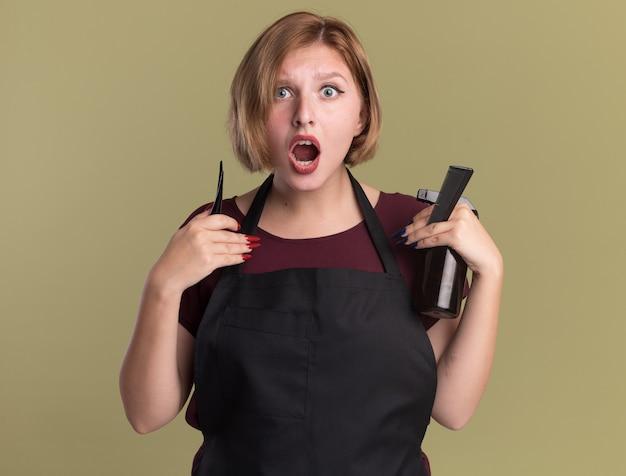 Молодая красивая женщина-парикмахер в фартуке держит бутылку с распылителем для заколки и расческу, смотрящую вперед, удивился, стоя над зеленой стеной