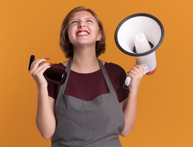 확성기와 스프레이 병을 들고 앞치마에 젊은 아름 다운 여자 미용사 오렌지 벽 위에 미친 행복하고 흥분 서