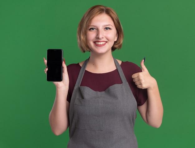 Молодая красивая женщина-парикмахер в фартуке, держа смартфон, глядя на фронт, весело улыбаясь, показывает палец вверх, стоя над зеленой стеной