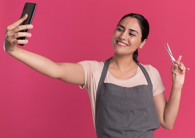 핑크 벽 위에 서 웃 고 가위를 보여주는 셀카를하고 그것을보고 스마트 폰을 들고 앞치마에 젊은 아름 다운 여자 미용사