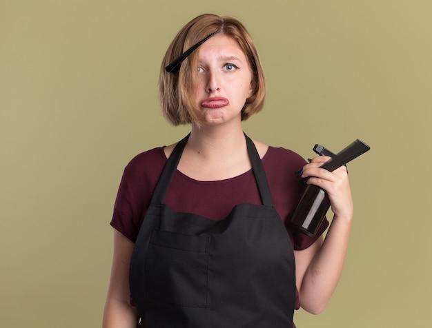 緑の壁の上に立っている唇をすぼめる悲しい表情で正面を見てスプレーボトルを保持しているエプロンの若い美しい女性美容師