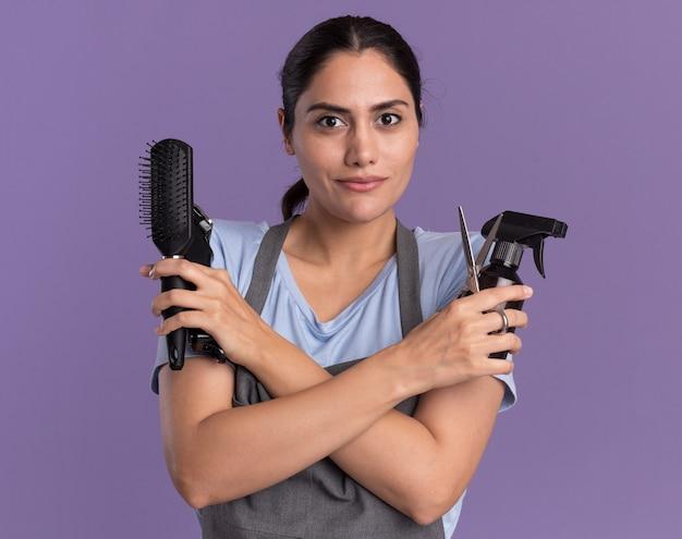 Молодая красивая женщина-парикмахер в фартуке, держащая триммер для баллончиков с распылителем и расческу для волос, глядя вперед с уверенным выражением лица, стоя у фиолетовой стены