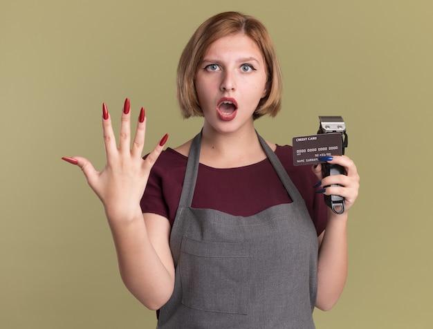 トリマーとクレジットカードを保持しているエプロンの若い美しい女性の美容師は、緑の壁の上に立っている5番を示して驚いて驚いた