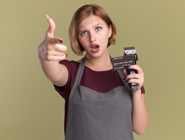 トリマーとクレジットカードを保持しているエプロンの若い美しい女性の美容師は、緑の壁の上に立って混乱し、不機嫌に人差し指で指しています