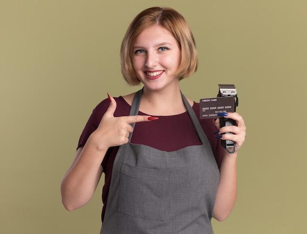トリマーとクレジットカードを保持しているエプロンの若い美しい女性の美容師は、緑の壁の上に立って幸せでポジティブな笑顔を人差し指で指しています