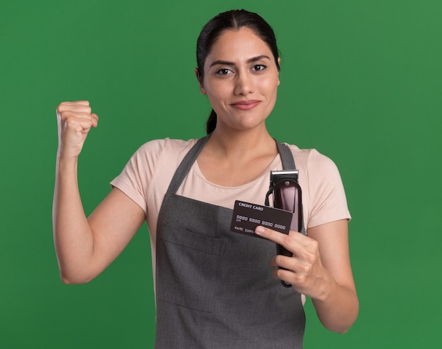 緑の壁の上に立っている自信を持って表情と勝者のように拳を上げるトリマーとクレジットカードを保持しているエプロンの若い美しい女性の美容師