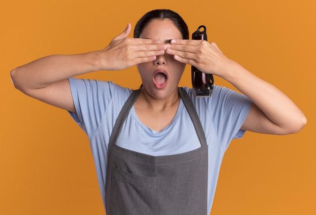 오렌지 벽 위에 손으로 눈을 감고 트리머를 들고 앞치마에 젊은 아름 다운 여자 미용사